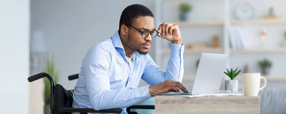 Student looks at scholarships on his laptop and struggles to determine whether an opportunity is a scam or not