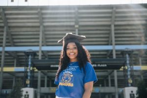 Independent student who just graduated smiles at the camera while wearing a graduation cap