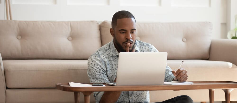 Student searches for scholarships on his laptop
