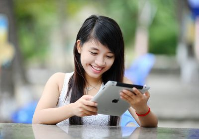 Female student sits outside and looks at her tablet as she chooses between taking out fixed and variable student loans