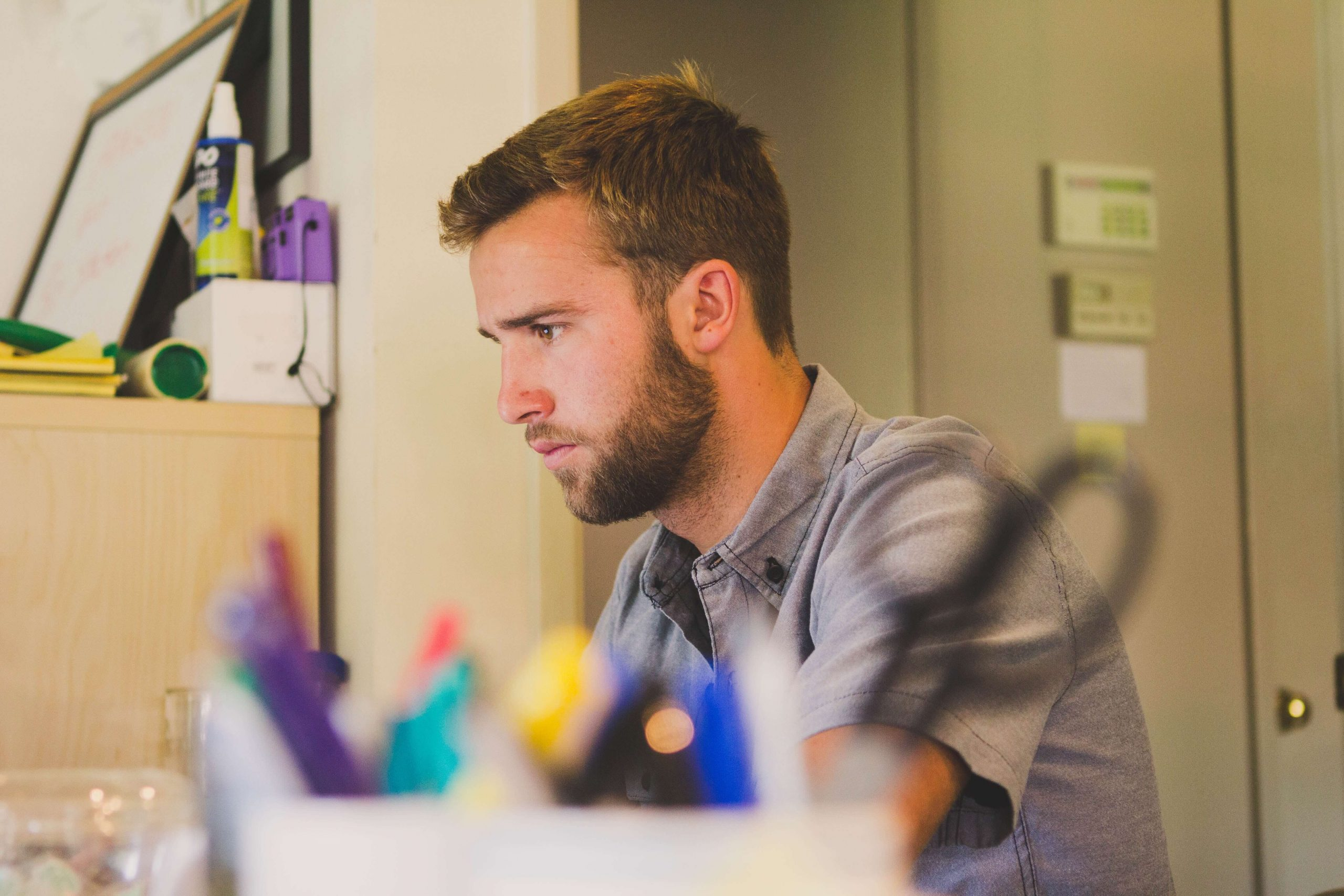 Student looks concentratedly at the computer as he compares private student loan options