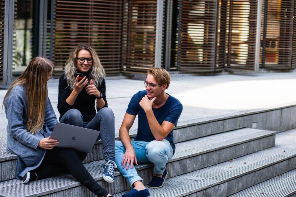 Students sit on steps at their school and discuss how to use the College Scorecard