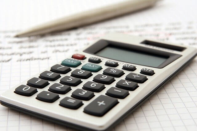 Calculator sits on top of a piece of paper and a pencil, which are being used to calculate whether or not scholarships are taxable