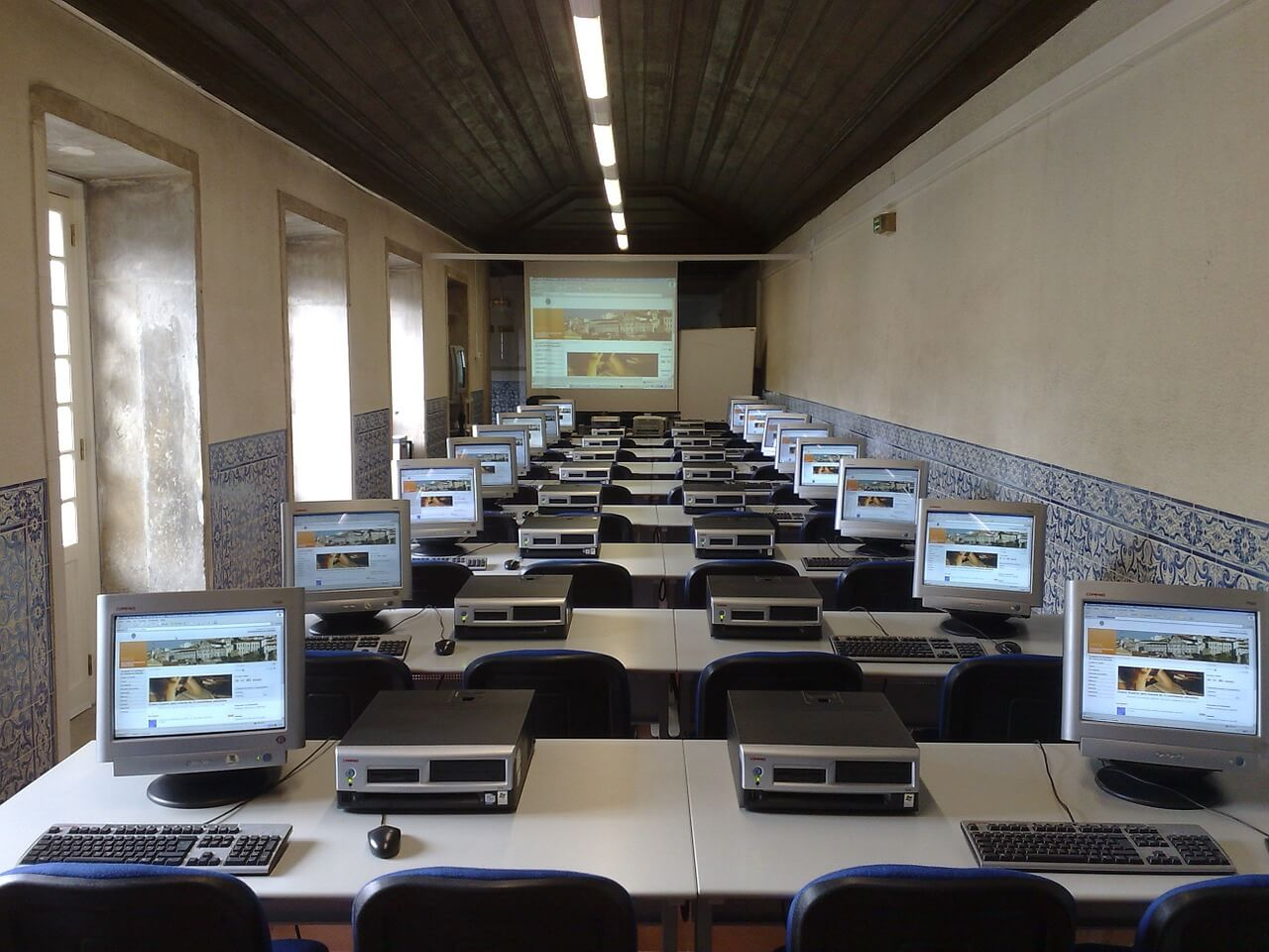 Photo of a classroom filled with computers with a projector screen in the front, which is used by a coding bootcamp