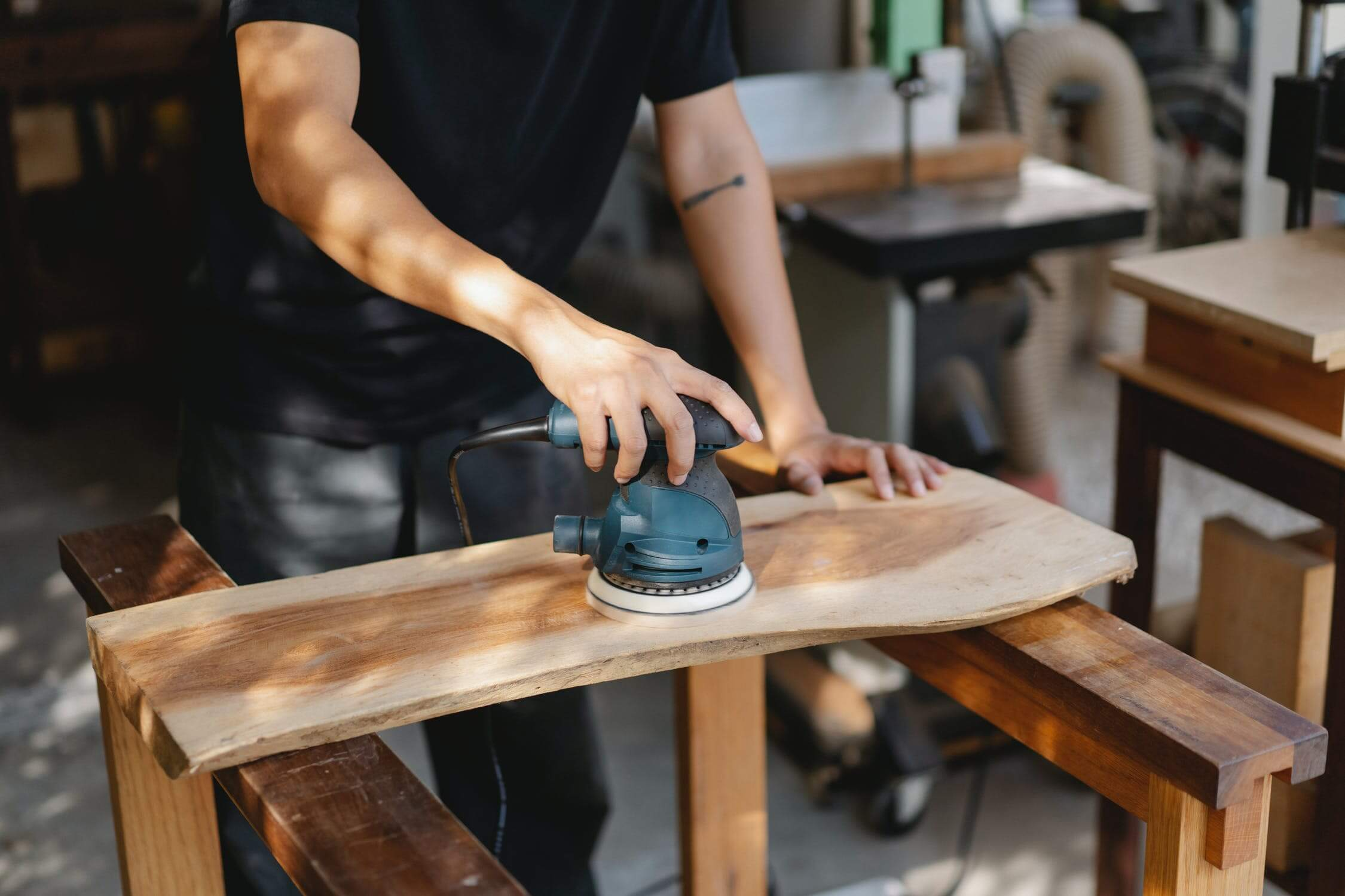 Trade school student cuts a piece of wood with an electric saw as he studies woodworking