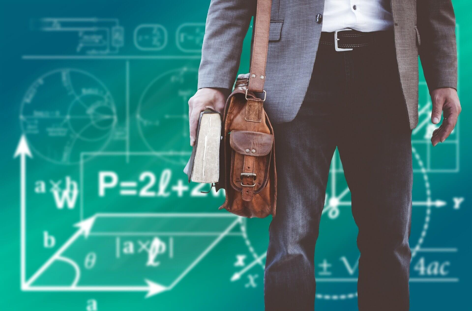 Education scholarship recipient stands in front of a chalkboard with scientific equations