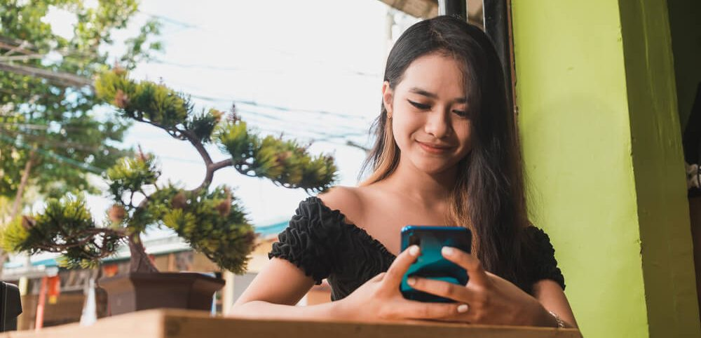 Female college student uses her phone to sell her clothes on the internet